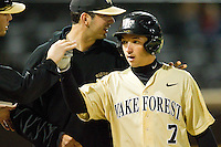 Joey Rodriguez (7) of the Wake Forest Demon Deacons high fives teammates after scoring a run in the 8th inning against the North Carolina State Wolfpack at Wake Forest Baseball Park on March 15, 2013 in Winston-Salem, North Carolina.  The Wolfpack defeated the Demon Deacons 12-6.  (Brian Westerholt/Four Seam Images)