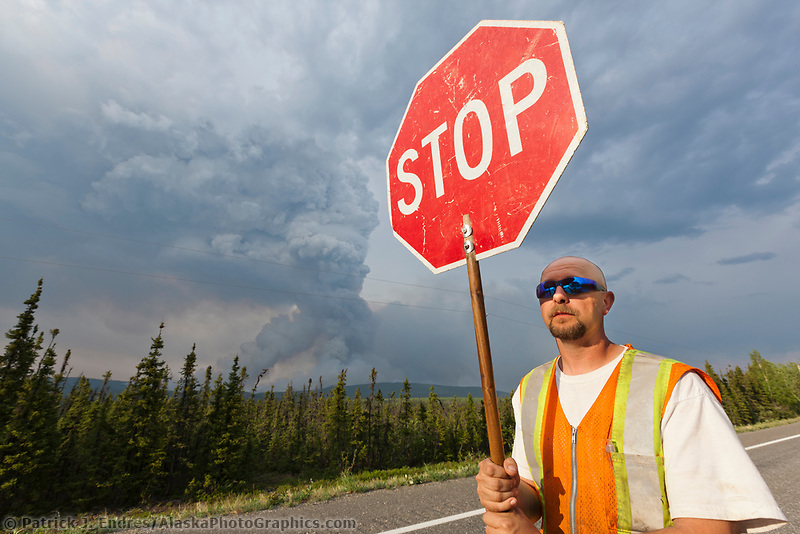 Road crew controls traffic along the Alaska Highway due to forest fire danger from the Eagle Trail forest fire near Tok, Alaska, May, 2010.