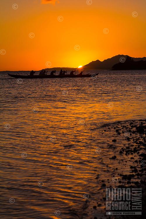Canoe paddlers in Hawai'i Kai as the sun sets behind Diamond Head, south shore, O'ahu.
