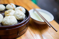 Small pork baozi rest on a steam tray near a bowl of xifan, or rice porridge or congee, at a breakfast shop with outdoor seating in a residential area of western Jiangbei district in Chongqing, China.