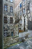 """UNGARN, 04.2009.Budapest - VII. Bezirk .Reste der Ghettomauer (Judenvernichtung 1944/45) im  alten Juedischen Viertel der Elisabethstadt (Erzs?betv?ros):  Die L-f?rmige Mauer auf den Hoefen der Sip utca 7 (links) und 5 (rechts) versperrte den Ausweg zur Dohany utca 26 (Mitte). Die Ghettogrenze verlief in Budapest nicht entlang von Strassen, sondern wurde hinter den Haeusern ueber Brandwaende und entsprechend verstaerkte Hofmauern gefuehrt, was Aufwand und Sichtbarkeit minimierte..Remains of the Ghetto wall (Holocaust 1944/45) in the old Jewish quarter of the """"Elizabethtown"""" district: The L-shaped wall in the courtyards of Sip street 7 (left) and 5 (right) cut off the exit to Dohany street 26 (middle). The ghetto boundary in Budapest did not follow open streets, but was drawn behind the houses using party walls and reinforced courtyard walls, thus minimizing effort and visibility..© Martin Fej?r/EST&OST"""