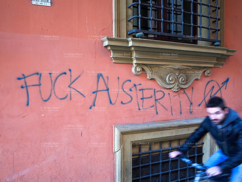 """Italy. Emilia-Romagna Region. Bologna. A man rides his bike and drives by a graffiti with written english words """" Fuck austerity"""" on a wall in the university neighborhood. 29.10.2014 © 2014 Didier Ruef"""