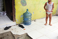 A young child stands near an empty water bottle in a slum community in central Jakarta. It is estimated over 25% of Indonesians live in slum areas, with more than 5 million people living in slum areas in the greater Jakarta area.