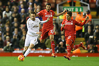 Swansea City's Gylfi Sigurosson Liverpool's Roberto Firmino and Emre Can during the Barclays Premier League match between Liverpool and Swansea City played at The Anfield Stadium on November 29th 2015