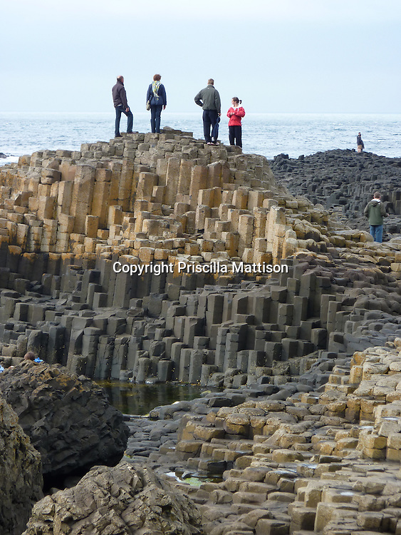 County Antrim, Northern Ireland - July 14, 2010:  Visitors stand on top of the interlocking basalt columns at the Giant's Causeway.