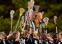 A group of female lacrosse players hold up their sticks in the air during a game.