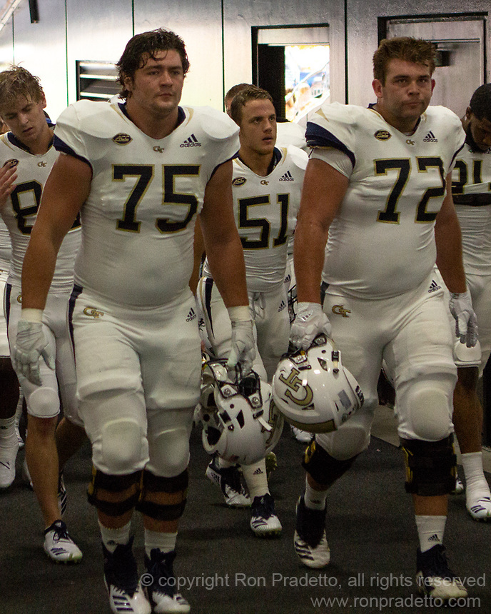 Georgia Tech players Parker Braun (75), Brant Mitchell (51) and Charlie Clark (72) leave the field after pregame warmups. The Pitt Panthers football team defeated the Georgia Tech Yellow Jackets 24-19 on September 15, 2018 at Heinz Field in Pittsburgh, Pennsylvania.