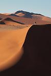 Tourist photographing sand dunes in Sossusvlei region of Namib-Naukluft National Park, Namibia.