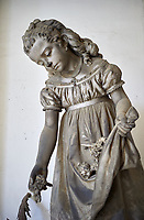 Picture and image of the stone sculpture of a young girl picking flowers in a Borgeoise Realistic style. The Grillo Family Tomb sulpted by G Scanzi 1876. Section D No 26, the monumental tombs of the Staglieno Monumental Cemetery, Genoa, Italy