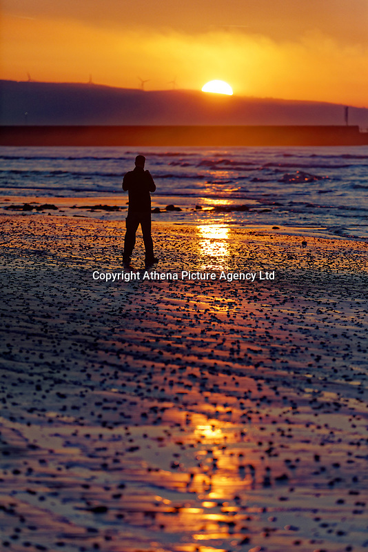 A man takes pictures as the sun rises over Swansea Bay in south Wales, UK. Tuesday 26 February 2019