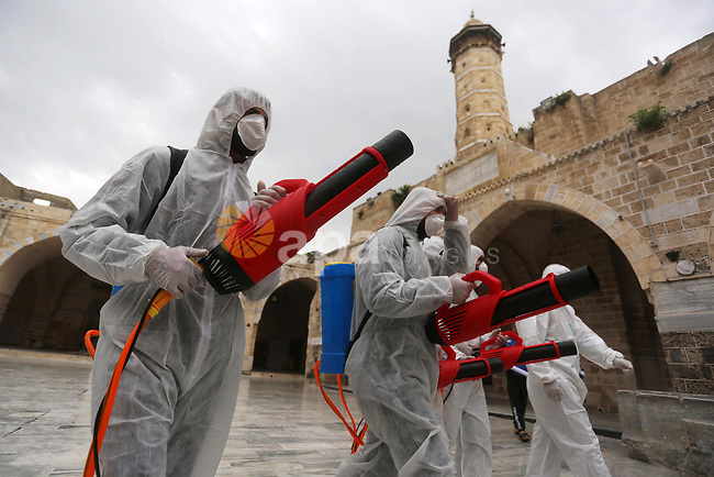 Palestinian workers disinfect Al-Omari Mosque, as a preventive measure amid fears of the spread of the novel coronavirus, in Gaza City on March 12, 2020. Photo by Ashraf Amra
