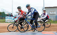 13 SEP 2014 - IPSWICH, GBR - Ollie Riley (centre) from Hethersett Hawks crosses the corner as Marcus Wadhams (left) from Birmingham Monarchs blocks his path during a second semi final heat at the  2014 British Open Club Cycle Speedway Championships  at Whitton Sports & Community Centre in Ipswich, Great Britain (PHOTO COPYRIGHT © 2014 NIGEL FARROW, ALL RIGHTS RESERVED)