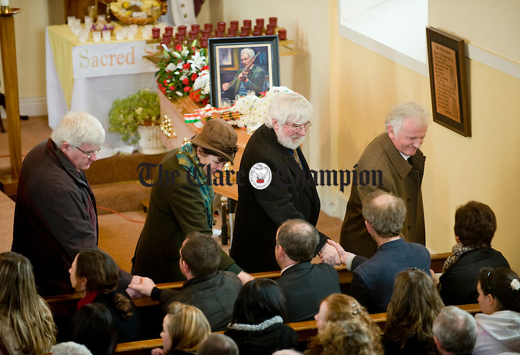 Mourners , including Joe Burke, sympathise with mourners at the funeral of Joe Ryan in Inagh. Photograph by John Kelly.