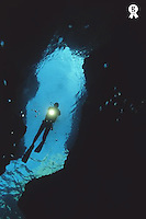 Scuba diver exploring underwater cave, shining torch, low angle view (Licence this image exclusively with Getty: http://www.gettyimages.com/detail/200388000-001 )