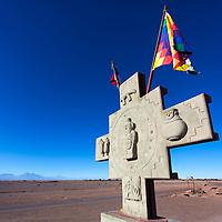 Stone Chakana Inca cross and colorful flags under Atacama Desert's blue sky, in El Valle de la Luna (Moon Valley) near San Pedro de Atacama, Chile
