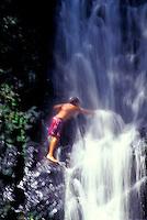 Boy playing at waterfall on the Big Island of Hawaii