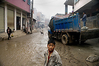 """A boy stands in the muddy streets of Sheng Cun, in Yuanyang County, Yunnan Province, China, while workers unload a truck full of concrete to be used to improve roads in the area.  """"Sheng Cun"""" is translated as """"Successful Village"""" in local tourist brochures."""