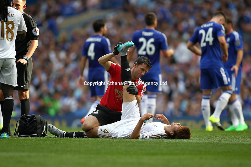 Ki Sung-Yueng of Swansea looks to be injured   during the Barclays Premier League match between  Chelsea and Swansea  played at Stamford Bridge, London