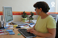 Female doctor  at computer, filling forms (Licence this image exclusively with Getty: http://www.gettyimages.com/detail/83676080 )