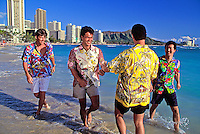Four attractive local young men wearing colorful aloha shorts goof around by the water's edge at Waikiki Beach with hotels and Diamond Head in the background.