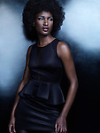 High fashion photo of a beautiful african american woman wearing a black dress on shiny background Image © MaximImages, License at https://www.maximimages.com