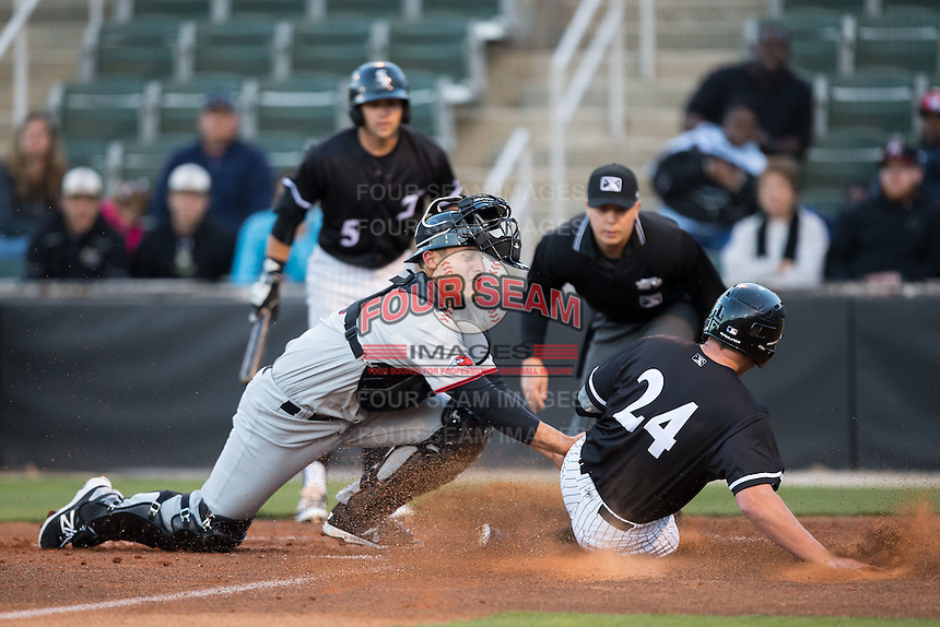 Hickory Crawdads catcher Tyler Sanchez (9) applies the tag to Zach Fish (24) of the Kannapolis Intimidators as home plate umpire Matt Carlyon looks on at Kannapolis Intimidators Stadium on April 8, 2016 in Kannapolis, North Carolina.  The Crawdads defeated the Intimidators 8-2.  (Brian Westerholt/Four Seam Images)
