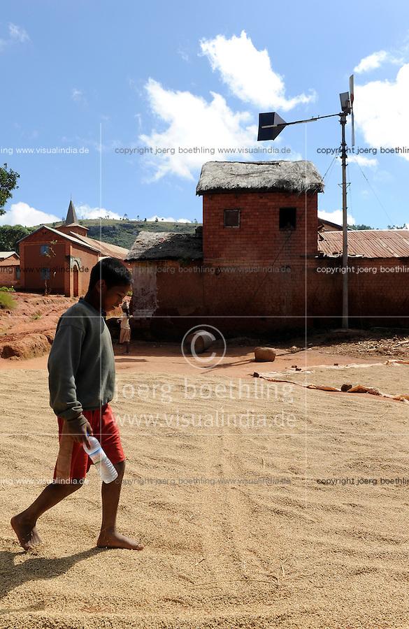 MADAGASCAR village Morarano with small wind turbine for rural off-grid electrification / MADAGASKAR , Junge wendet Reis zum Trocknen, Dorf Morarano mit kleiner Windkraftanlage zur laendlichen Elektrifizierung