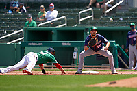 Minnesota Twins first baseman Alex Kirilloff (19) waits for a throw as J.D. Martinez (28) dives back to the bag during a Major League Spring Training game against the Boston Red Sox on March 17, 2021 at JetBlue Park in Fort Myers, Florida.  (Mike Janes/Four Seam Images)