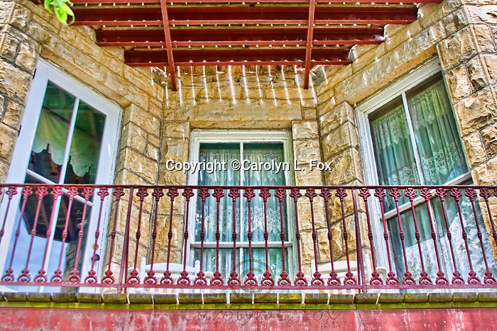 Windows and the railing of an old hotel make a picturesque sight.