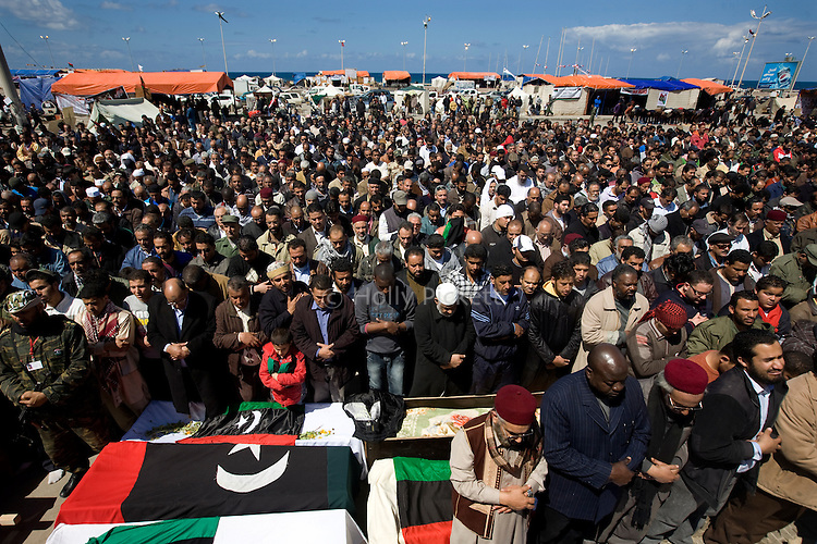 Men pray over the bodies of those killed during fighting between opposition rebels and loyalist forces of Col. Muammar Qaddafi, in Benghazi Libya, March 20, 2011. The main hospital in Benghazi reported around 50 dead fighters and civilians the previous day and at least 35 on Sunday.
