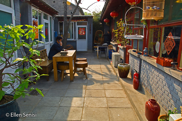 Beijing, China / April 2007.Man sits at table in interior courtyard of traditional Chinese home in hutong neighborhood. Hutong is a unique form of housing community that exists only in China. Traditional courtyard-style residences are clustered together and separated by narrow alleys. Most Beijing hutong homes were built in the Ming or Qing Dynasties (1368-1911).  .© Ellen B. Senisi
