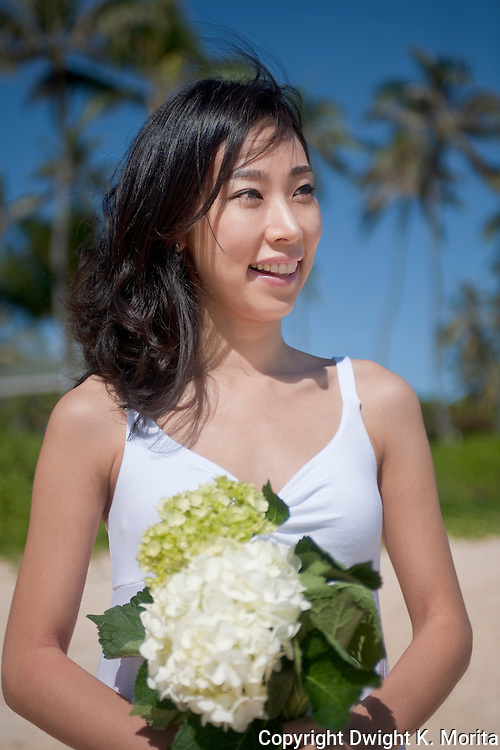 Asian bride awaits her groom to stroll on Lanikai beach as they look forward to their life as a married couple following their wedding.