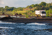 Bali, Indonesia.  Trucks Pick up Black Volcanic Soil from River Bed to Take to Fields for Enriching the Soil.