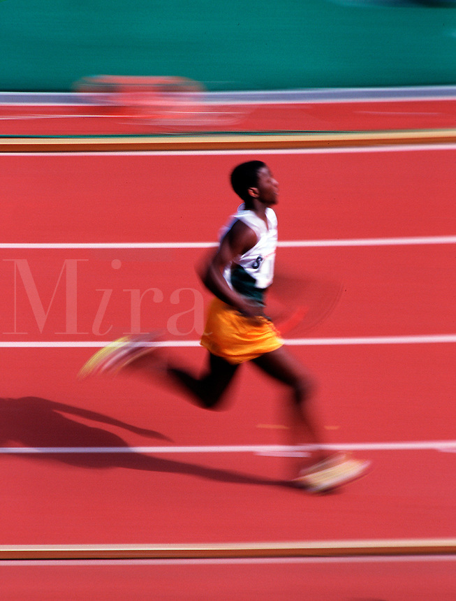 Action image of a male runner in motion at a track meet.