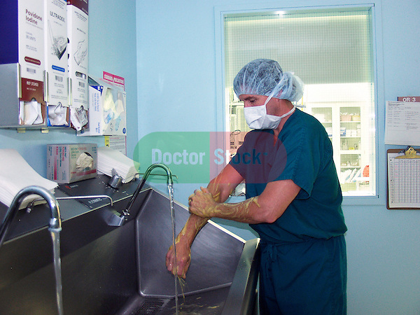 surgeon washing hands, scrubbing in sink outside operating room