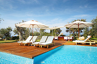 Sun-loungers and parasols are arranged on a wooden decked terrace beside a swimming pool.