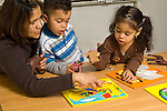 Education preschool 2-3 year olds horizontal female teacher working with boy and girl playing with puzzles