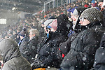 Oldham fans try to keep warm in the snow. Oldham v Portsmouth League 1