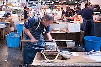 A man works at a whetstone sharpening knives at Tsukiji Fish Market, Tokyo, Japan.