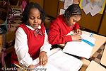 K-8 Parochial School Bronx New York Grade 3 mathematics lesson on measurement using rulers two girls working at desks horizontal
