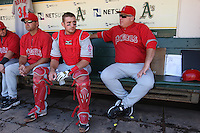 OAKLAND, CA - OCTOBER 3:  Jeff Mathis #5 and manager Mike Scioscia #14 of the Los Angeles Angels of Anaheim get ready in the dugout before the game against the Oakland Athletics at the Oakland-Alameda County Coliseum on October 3, 2009 in Oakland, California. Photo by Brad Mangin
