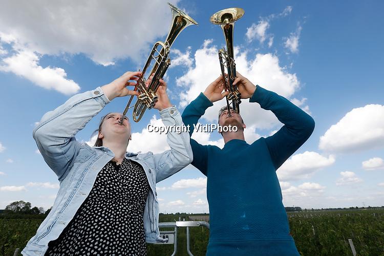 Foto: VidiPhoto<br /> <br /> DODEWAARD - Broer en zus Herman en Liesbeth de Vree oefenen maandagmiddag op een hoogwerker tussen de perenbomen gezamenlijk met hun trompet, de taptoe die ze maandagavond tijdens de dodenherdenking afzonderlijk op twee verschillende plaatsen zullen spelen. Herman speelt in de kerk van Opheusden, zodat met name eenzame ouderen online kunnen meeluisteren. Liesbeth speelt vanuit de toren van de hervormde kerk in Valburg. De taptoe is een eerbetoon aan de slachtoffers van de Tweede Wereldoorlog. Het Nationaal Comité 4 en 5 mei nodigt geoefende spelers van blaasinstrumenten uit om twee minuten voor acht het taptoe-signaal mee te spelen. Broer en zus De Vree, leden van een muzikaal fruittelersgezin, zijn geoefende 'blazers'.
