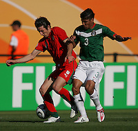 JUNE 11, 2006: Nuremberg, Germany: Mexican defender (3) tries to take the ball away from Iranian midfielder (14) Andranik Teymourian during the World Cup Finals at Franken-Stadion in Nuremberg, Germany.  Mexico defeated Iran, 3-1.