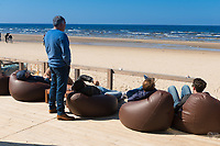 People relaxing in soft chairs on the open terrace of the cafe, enjoying the Baltic sea in Jurmala, Latvia