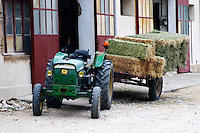 An old rusty green tractor John Deere drawing a cart filled with hay bales parked outside a farm Bouches du Rhone, France Europe
