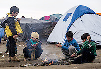 Pictured: Young boys try to keep warm at the camp Monday 29 February 2016<br /> Re: A crowd of migrants has burst through a barbed-wire fence on the FYRO Macedonia-Greece border using a steel pole as a battering ram.<br /> TV footage showed migrants pushing against the fence at Idomeni, ripping away barbed wire, as FYRO Macedonian police let off tear gas to force them away.<br /> A section of fence was smashed open with the battering ram. It is not clear how many migrants got through.<br /> Many of those trying to reach northern Europe are Syrian and Iraqi refugees.<br /> About 6,500 people are stuck on the Greek side of the border, as FYRO Macedonia is letting very few in. Many have been camping in squalid conditions for a week or more, with little food or medical help.