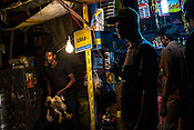 A shop vendor pulls out a chicken for his customer in his shop in Anandopur in Kolkata, West Bengal, India.