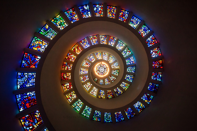 """The most prominent and recognizable feature of Thanks-Giving Square is the Chapel of Thanksgiving, a small, spiral tower that features an enclave for prayerful thanks. The entrance to the chapel is at the end of a 125-foot bridge that runs over a cascading waterfall. Inside the chapel, the spiral is topped with stained glass """"Glory Window"""", one of largest horizontally mounted stained-glass pieces in the world. The window was designed by Gabriel Loire of Chartres, France to feature brighter colors as the spiral reached its apex, becoming brighter as it reaches the center. The etched glass window """"The Spirit of Thanksgiving,"""" designed by glass engraver John Hutton, features a dove over the doorway."""
