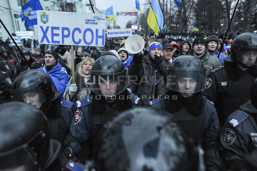 """Supporters of president Yanukovich near the building of Parliament cheering """"go back to work"""" to demontrators. It is widely known that most of people who go on the streets to support current government are paid daily around 20 US dollars. Their meetings are usually guarded by Police to prevent violence between two sides of protesters."""
