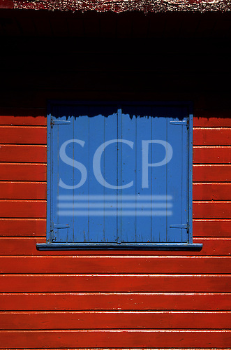 Buenos Aires, Argentina. Brightly painted blue window shutters in a red wall in the La Boca district.